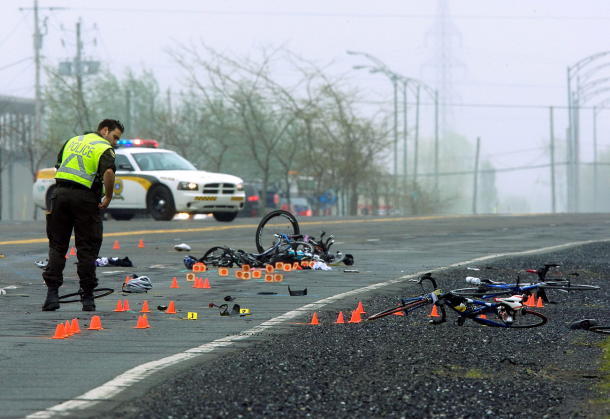 Police examine the scene where a pickup truck struck a group of cyclists on May 14, 2010, in Rougemont, Quebec, south of Montreal.