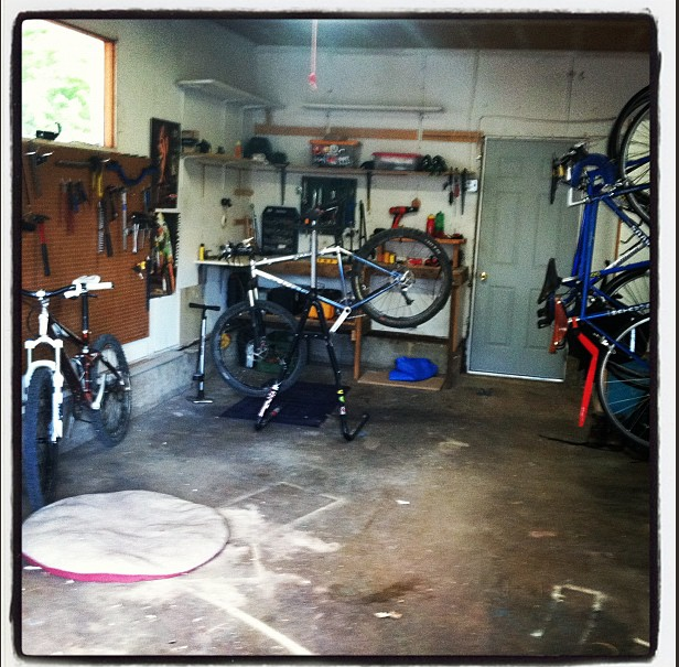 "It's got all the essentials: pegboard for tools, doggy bed for dog, newly repaired Gunnar mountain bike, hot poster of naked April Lawyer on the wall, bottle opener courtesy of ""El Jefe"" Miller, and enough space to hang lots o bikes. Fucking Heaven."